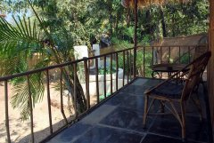 Secret Garden - The balcony of an eco-friendly coconut leaf beach hut at Secret Garden in Colomb Bay, Goa